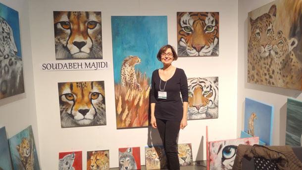 سودابه مجیدی در نمایشگاه در مقابل نقاشی هایش