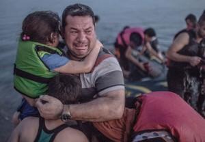 پناهجوی سوری پس از رسیدن به ساحل یکی از جزایر یونان، در حالی که منقلب شده دو فرزندش را در آغوش گرفته است.